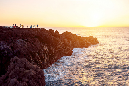 los hervideros: Los Hervideros rocky coast with tourists on the sunset on Lanzarote island in Spain