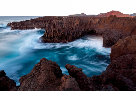 los hervideros: Los Hervideros rocky coast with wavy ocean and volcanos on the background on the sunset on Lanzarote island in Spain. Long exposure effect with blurred water