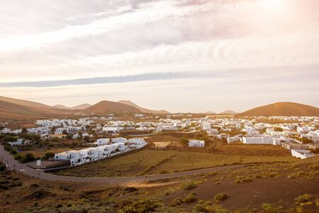 volcanos: View on traditional whitewashed village with volcanos on the background in the morning on Lanzarote island in Spain