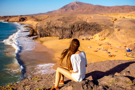 sea cliff: Young female tourist sitting and enjoying beautiful view on Papagayo beach on Lanzarote island in Spain