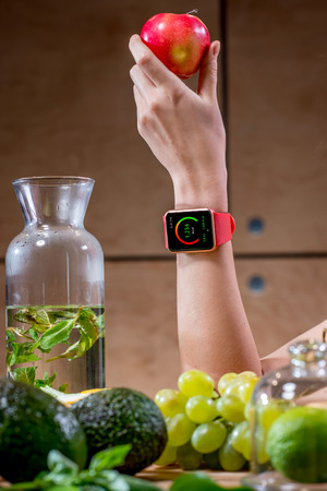 Female hand with smart watch showing calories and green fruits on the foreground. Smart watch technology for healthcare Stock Photo