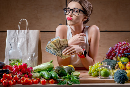 dispirited: Dispirited young woman counting money for buying expensive natural food. High price of healthy natural food