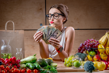 Dispirited young woman counting money for buying expensive natural food. High price of healthy natural food