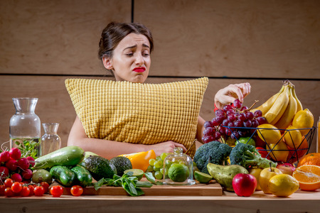 Sad woman with pillow watching reluctantly at the fuits and vegetables in the morning or in the evening before sleeping. Diet and healthy food concept Reklamní fotografie