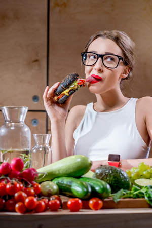 grieved: Young sport woman choosing between burger and healthy but tasteless food at the table full of fruits and vegetables in the wooden kitchen interior
