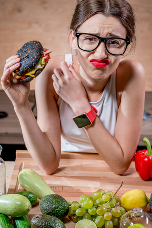 wry: Young sport woman choosing between burger and healthy but tasteless food at the table full of fruits and vegetables in the wooden kitchen interior
