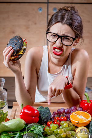 dispirited: Young sport woman choosing between burger and healthy but tasteless food at the table full of fruits and vegetables in the wooden kitchen interior