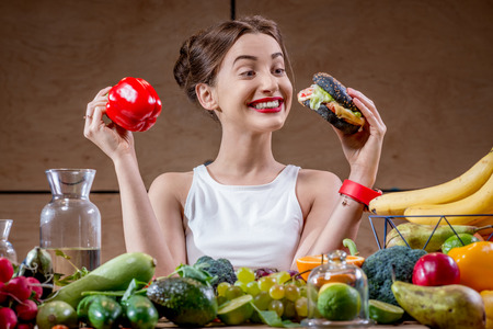 between: Young sport woman choosing between burger and healthy but tasteless food at the table full of fruits and vegetables in the wooden kitchen interior