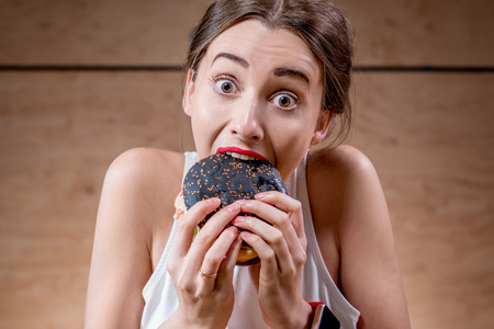 adult sandwich: Young and hungry woman eating black burger on the wooden background