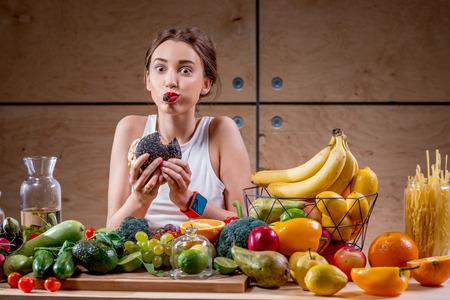 Hongerige vrouw die zwarte hamburger bij de tafel vol met groenten en fruit op de houten achtergrond. Kiezen tussen gezonde en ongezonde voeding
