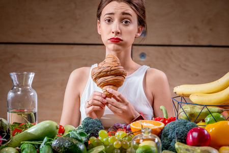 between: Young woman feeling sorry for eating sweet croissant instead of healthy fruits and vegetables. Worry about calories and weight