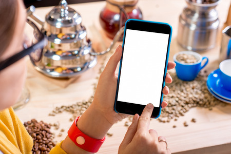 copy sapce: Female hand holding smart phone with white screen on the background full of various equipment for alternative coffee brewing