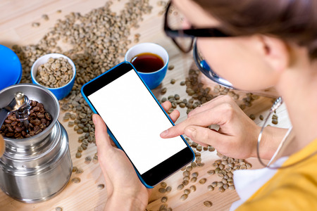 copy sapce: Woman using smart phone with white screen on the table with coffee beans, cups and grinder Stock Photo
