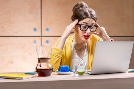 shoked: Surprised woman in glasses and yellow sweater working or studying with laptop on the table with coffee and noteboooks in the wooden interior Stock Photo