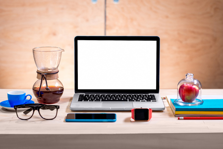 Laptop with white screen on the wooden workplace with coffee, glasses, notebooks, apple, watch and smart phone
