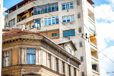 suffered: SARAJEVO, BOSNIA and HERZOGOVINA - CIRCA JUNE 2015: Buildings with holes from bullets in Sarajevo. From 1992 to 1996 the city suffered during the Bosnian War