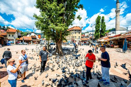 squire: SARAJEVO, BOSNIA - HERZOGOVINA - CIRCA JUNE 2015: Crowded old market squire with pigeons on the north bank of the river Miljacka in the municipality of Stari Grad in Sarajevo.