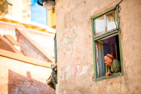 out of town: SIBIU, ROMANIA - CIRCA JUNE 2015: Elder woman looks out the window in old building in Sibiu old town in Romania. Life on pension in Romania Editorial