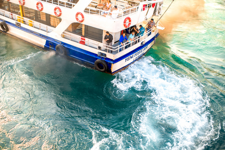 crowded space: ISTANBUL -�� MAY 28, 2015: Top view on the ferry with people floats on the blue and green water throwing into the air harmful gases in Bosphorus waterway in Istanbul. Ecology problems in Istanbul