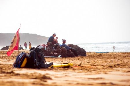 surfers: EL COTILLO, FUERTEVENTURA ISLAND, SPAIN - SIRCA JANUARY 2016: Surfers rest on El Cotillo sandy beach. El Cotillo beach is very popular for surfing on Fuerteventura island Editorial