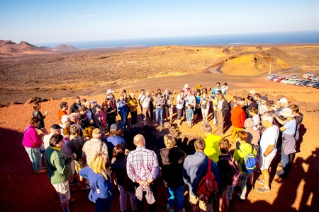 manrique: TIMANFAYA PARK, LANZAROTE ISLAND, SPAIN - SIRCA JANUARY 2016: Tourits near volcanic heating system in Timanfaya park. This park is entirely made up of volcanic soil and was designed by Cesar Manrique