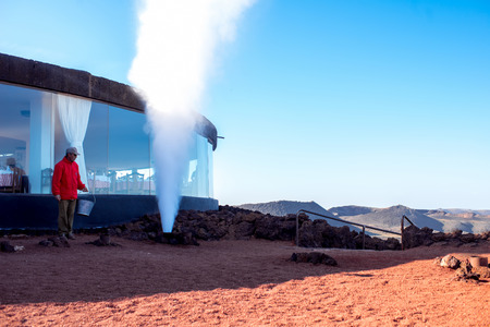 timanfaya natural park: TIMANFAYA PARK, LANZAROTE ISLAND, SPAIN - SIRCA JANUARY 2016: Man shows natural geyser for tourists in Timanfaya park. This park is entirely made up of volcanic soil and was designed by Cesar Manrique Editorial