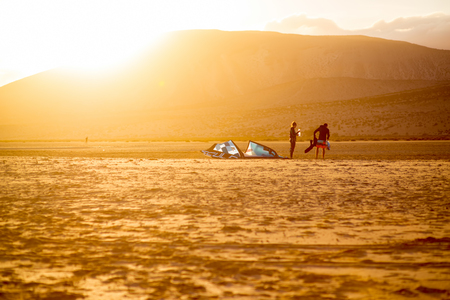 windsurfers: JANDIA, FUERTEVENTURA ISLAND, SPAIN - SIRCA JANUARY 2016: Couple windsurfers after the training on Sotavento beach on the sunset. Fuerteventura island is very popular island for surfing Editorial