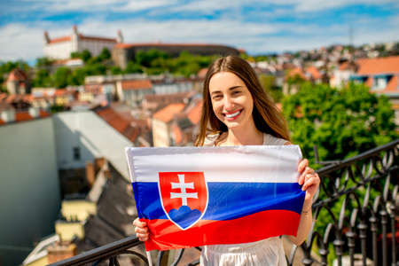 promoting: Young female tourist holding slovak flag in Bratislava city. Promoting tourism in Slovakia Stock Photo