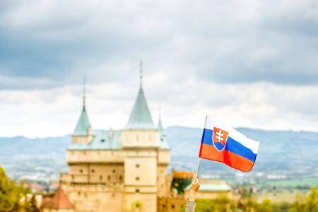 slovak: Bojnice castle with slovak flag in Slovakia