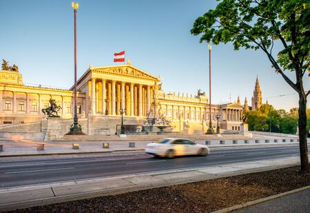 athena: Austrian parliament building with Athena statue on the front in Vienna on the sunrise. Long exposure image technic with burred car Stock Photo