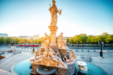athena: Athena statue near Parlament building with Vienna cityscape and old tram on the background on the sunrise
