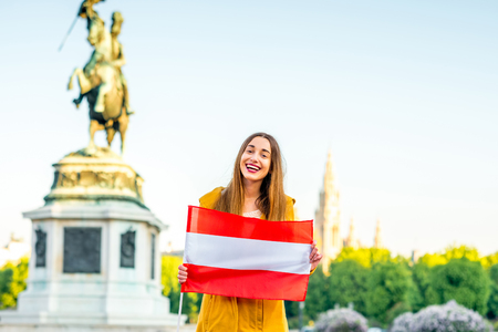 archduke: Young smiling woman holding austrian flag on Helden square in Vienna. Stock Photo