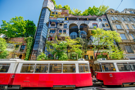 expressionist: VIENNA, AUSTRIA - CIRCA APRIL 2016: Colorful apartment house   named Hundertwasserhaus with red tram in Vienna. This building is famous expressionist landmark designed by artist Friedensreich Hundertwasser