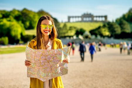 gloriette: Young female tourist traveling with paper map in Schoenbrunn palace with Gloriette building on the background