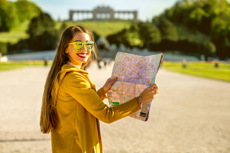schoenbrunn: Young female tourist traveling with paper map in Schoenbrunn palace with Gloriette building on the background