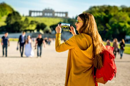 gloriette: Young female tourist photographing with phone Gloriette building in Schoenbrunn palace in Vienna