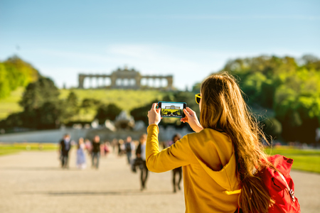 schoenbrunn: Young female tourist photographing with phone Gloriette building in Schoenbrunn palace in Vienna