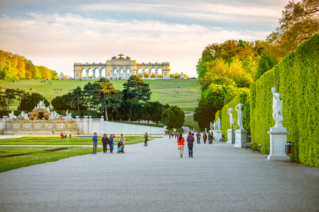 VIENNA, AUSTRIA - CIRCA APRIL 2016: Gloriette building in Schonbrunn gardens with tourist walk on the alley in Vienna. Schonbrunn Palace is one of the most important architectural monuments in Austria 新闻类图片