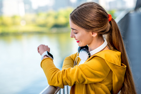 megacity: Young sport woman in yellow sweater looking at smart watch on the modern bridge with skyscrapers on the background. Morning exercise in megacity