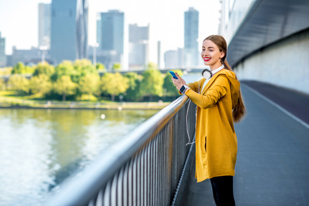 megacity: Young sport woman in yellow sweater using smart phone on the modern bridge with skyscrapers on the background. Morning exercise in megacity