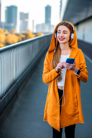 megacity: Young sport woman in yellow sweater listening to the music with smart phone on the modern bridge with skyscrapers on the background. Morning exercise in megacity