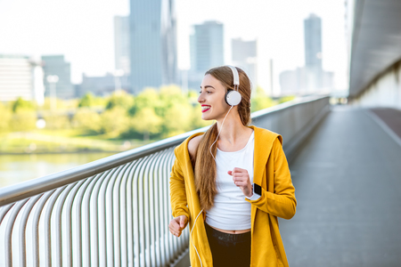 megacity: Young sport woman in yellow sweater with earphones running on the modern bridge with skyscrapers on the background. Morning exercise in megacity