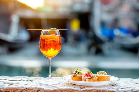 Spritz Aperol bebida con venecianas cicchetti aperitivos tradicionales en el fondo chanal agua en Venecia. aperitivo italiano Traditioanal. Imagen con la pequeña profundidad del campo