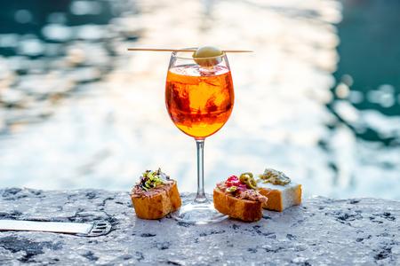 ヴェネツィア水の運河背景にヴェネツィアの伝統的なスナック cicchetti Aperol 飲み物をさっと振りかけます。Traditioanal イタリアの食前酒。小さな被写