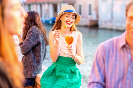 Young woman with glass of Spritz Aperol sitting near the water chanal in Venice on the sunset. Traditional italian appetizer drink. Image with small depth of field Reklamní fotografie