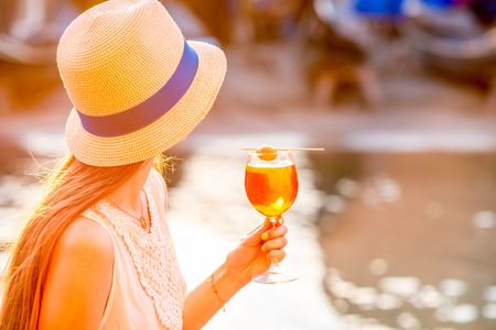 Young woman with glass of Spritz Aperol sitting near the water chanal in Venice on the sunset. Traditional italian appetizer drink. Image with small depth of field Stock Photo