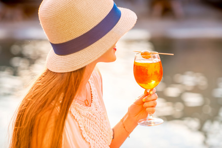 spritz: Young woman with glass of Spritz Aperol sitting near the water chanal in Venice on the sunset. Traditional italian appetizer drink. Image with small depth of field Stock Photo