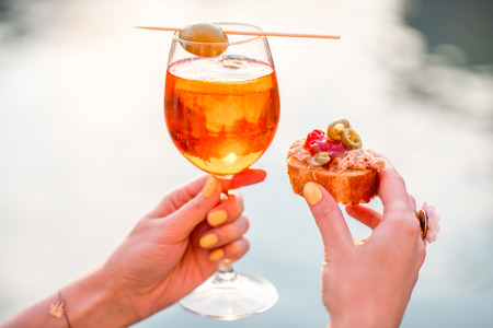 Female hand holding glass with Spritz Aperol alcohol drink decorated with olive on the water chanal background in Venice. Image with small depth of field