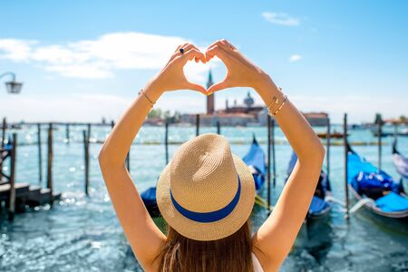 Woman making heart shape with hands on the beautiful view in Venice. Venice is one of the favorite tourist city Stock Photo