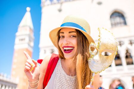 Young female traveler pointing with finger on San Marco tower holding carnaval mask in Venice. Happy traveling in Venice Stock Photo